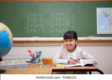 Smiling schoolgirl drawing on a coloring book in a classroom