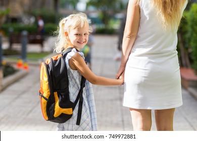 Smiling Schoolgirl Holding Mother Hand
