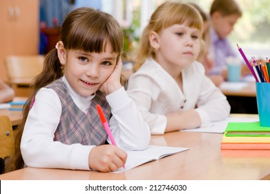 smiling schoolgirl looking at camera during lesson