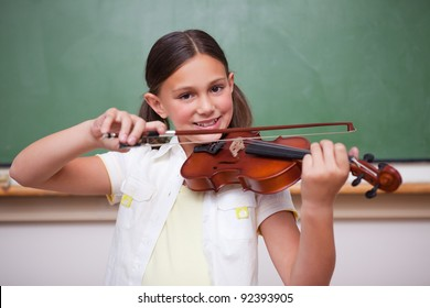 Smiling schoolgirl playing the violin in a classroom