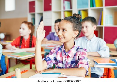 Smiling schoolgirl raising her hand at lesson