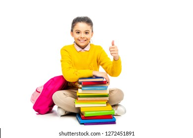 smiling schoolgirl sitting near stack of books and pink backpack, looking at camera and showing thumb up isolated on white