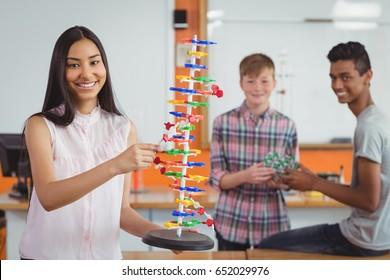 Smiling schoolgirl studying molecule model in laboratory at school
