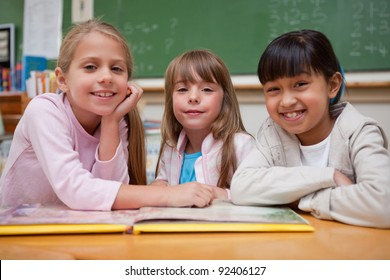 Smiling schoolgirls reading a fairy tale to their classmate while looking at the camera