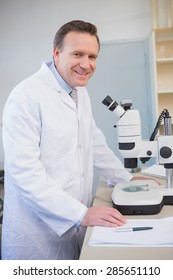 Smiling scientist examining sample with microscope in the laboratory