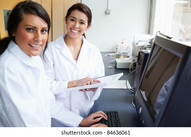 Smiling scientists posing with a monitor in a laboratory