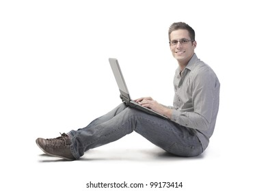Smiling seated young man using a laptop