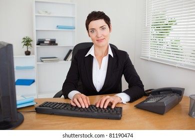 Smiling secretary typing on her keyboard in her office