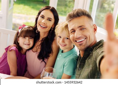 Smiling for selfie. Beaming cheerful children smiling while making selfie with mom and dad