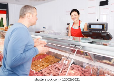smiling  seller helping attentive male customer choosing different sausages in butcher's shop