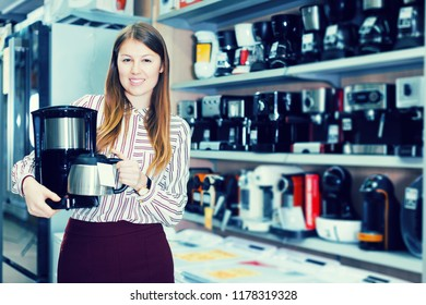 Smiling seller showing coffeemaker in domestic appliances section