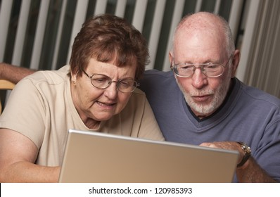 Smiling Senior Adult Couple Having Fun on the Computer Laptop Together.
