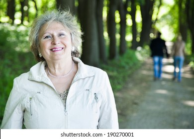 smiling senior aged woman outdoors with blurred walking couple