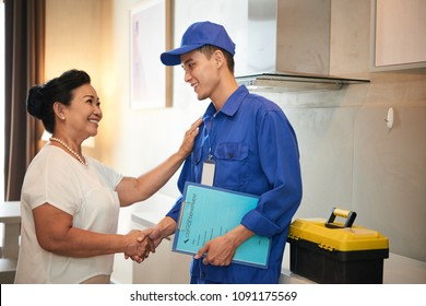 Smiling senior Asian woman saying thanks to repairman
