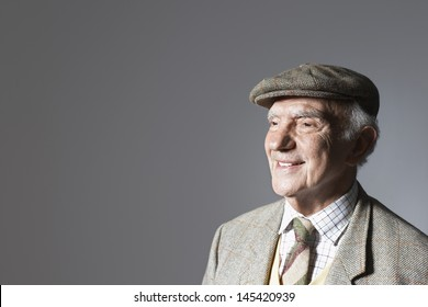 Smiling senior businessman in flat cap against gray background