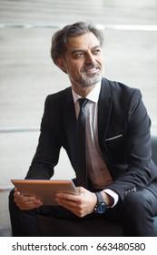 Smiling senior businessman holding digital tablet