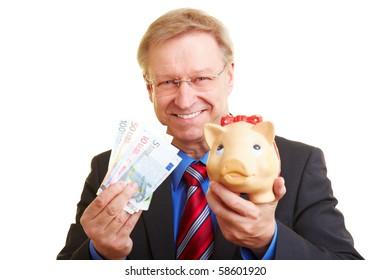 Smiling senior businessman holding piggy bank and banknotes