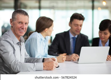 Smiling senior businessman at meeting with team