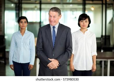 Smiling senior businessman with multiethnic team