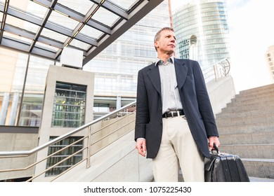 Smiling senior businessman portrait in the city. Caucasian man on his late fifties, wearing smart casual clothes and holding a suitcase. Business and city life concepts.