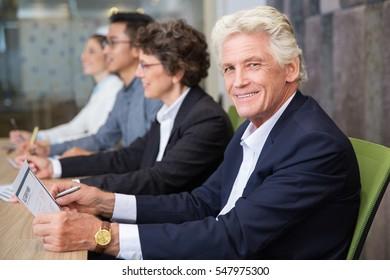Smiling senior businessman sitting at seminar