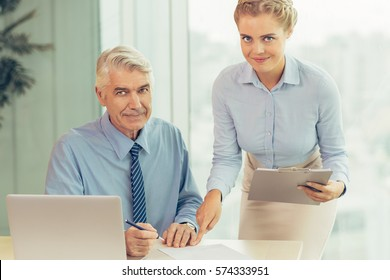 Smiling senior businessman with young secretary