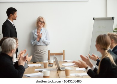 Smiling senior businesswoman boss and team clapping hands at meeting, happy woman executive applauding celebrating business success or congratulating african manager with promotion at group meeting