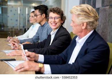 Smiling senior businesswoman sitting at meeting