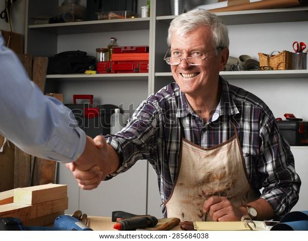 Smiling senior carpenter greeting customer and shaking his hand at workshop. Small business.