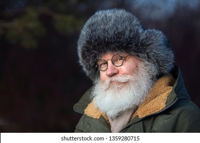 Smiling senior caucasian man in vintage eyeglasses poising against dark nature. Closeup portrait of elderly stylish hipster with splendid mustache and beard and fur cap. Copy space.