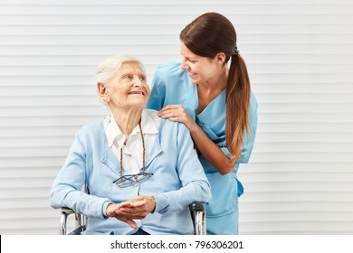 Smiling senior citizen in wheelchair and nurse at the elderly care in retirement home