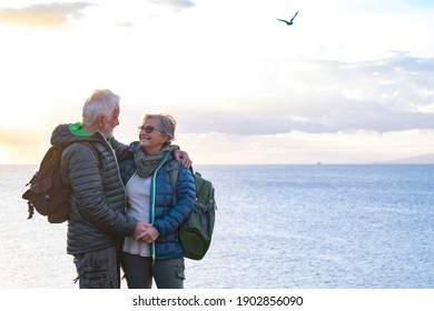 Smiling senior couple with backpack on their back enjoys the hike on the ocean cliffs. On the horizon the profile of an island and a ship.