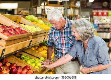Smiling senior couple buying apples at the grocery shop