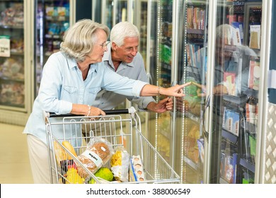 Smiling senior couple with cart buying food at the supermarket