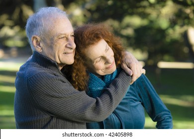 Smiling Senior Couple Embracing Each Other in a Park