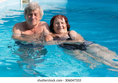 Smiling senior couple enjoying time together in a swimming pool on a sunny day