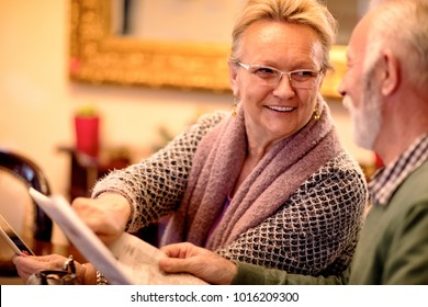 Smiling senior couple having fun while reading newspaper and using tablet