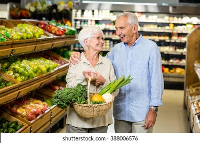 Smiling senior couple holding basket with vegetables at the grocery shop