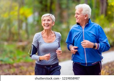 Lächelndes Seniorenpaar joggen im Park