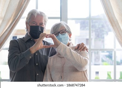 A smiling senior couple look at camera wearing surgical protective mask, making hear shape with their hands - in lockdown at home due to the coronavirus infection