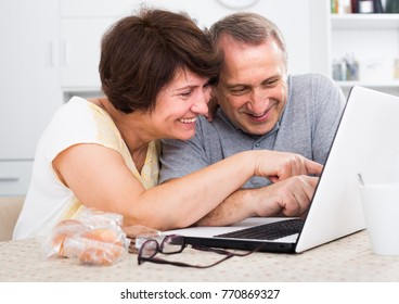 Smiling senior couple looking documents on laptop indoors at home together.  Focus on woman