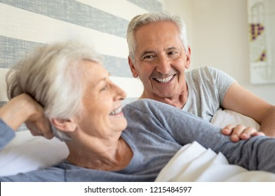 Smiling senior couple lying on bed on a bright sunny morning. Happy old man lay near his wife in bed. Mature couple having fun together in bedroom.