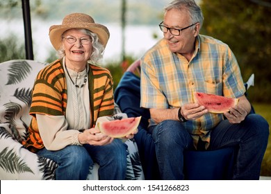 Smiling senior couple on romantic vacation eating watermelon