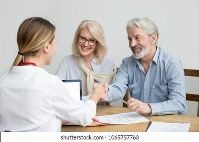 Smiling senior couple and realtor handshaking making real estate deal, older man and mortgage broker shaking hands, aged family buyers agree to make investment or purchase new house at meeting
