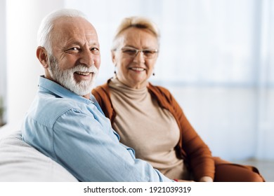 Smiling senior couple  sitting at home. There are looking at camera