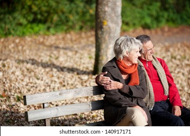 Smiling senior couple sitting on the bench park while looking at something