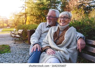 Lächelndes Ehepaar, das auf der Bank im Park sitzt und zusammen in den Ruhestand tritt