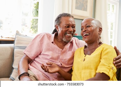 Smiling Senior Couple Sitting On Sofa At Home Together