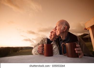 Smiling senior couple sitting outside at sunset