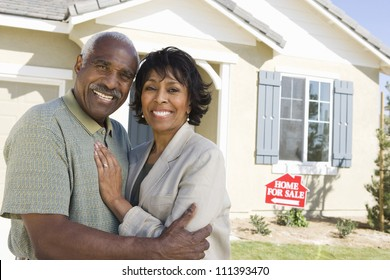 Smiling senior couple standing in front of house for sale